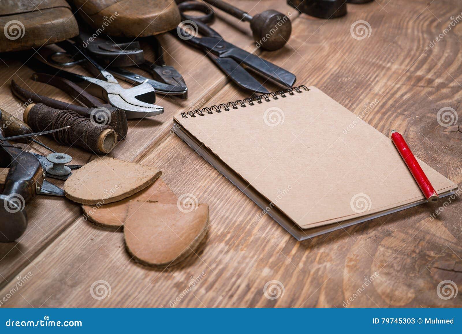 Sistema de herramientas, cuaderno, lápiz para el zapatero en un fondo de madera