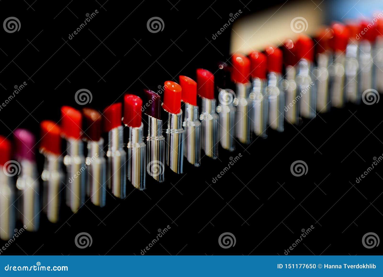 Sistema de l?piz labial Diversas sombras del color rojo Fije de la barra de labios, colección en fondo negro Rostro y maquillaje