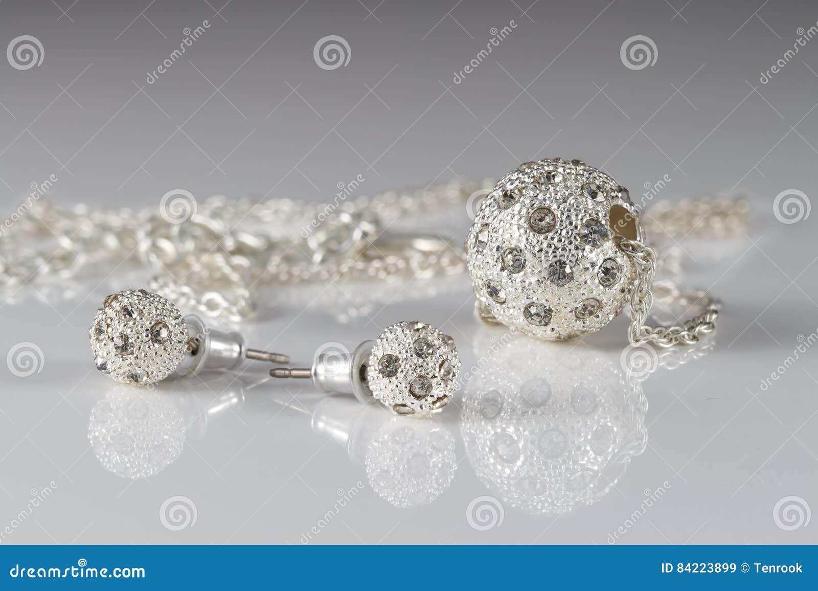 Sistema de la joyería del primer de pendientes y del colgante de plata tachonados en superficie de acrílico en fondo gris