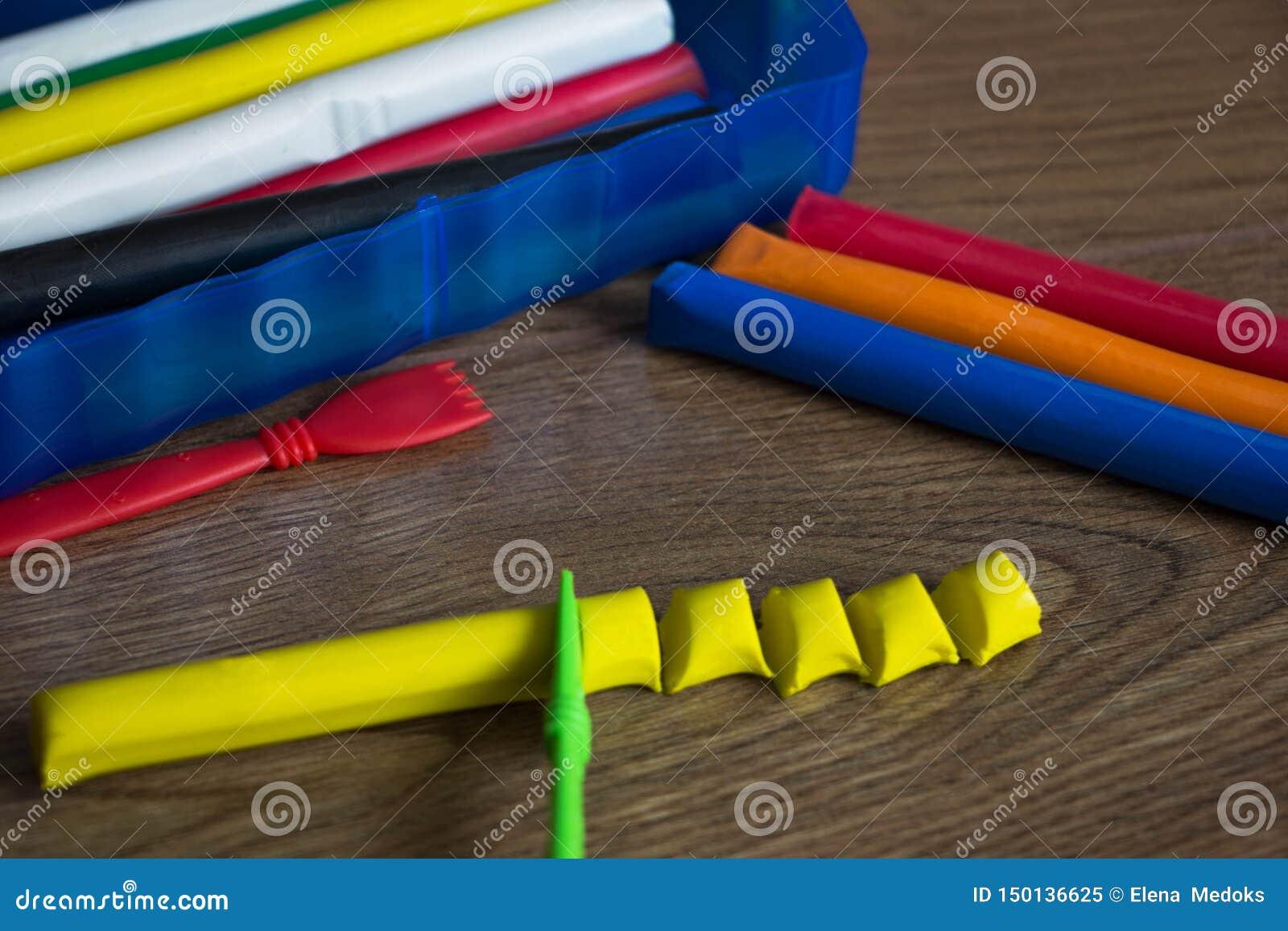 Sistema de las barras multicoloras del plasticine para modelar en la tabla de madera Concepto de la visi?n superior, de la salida