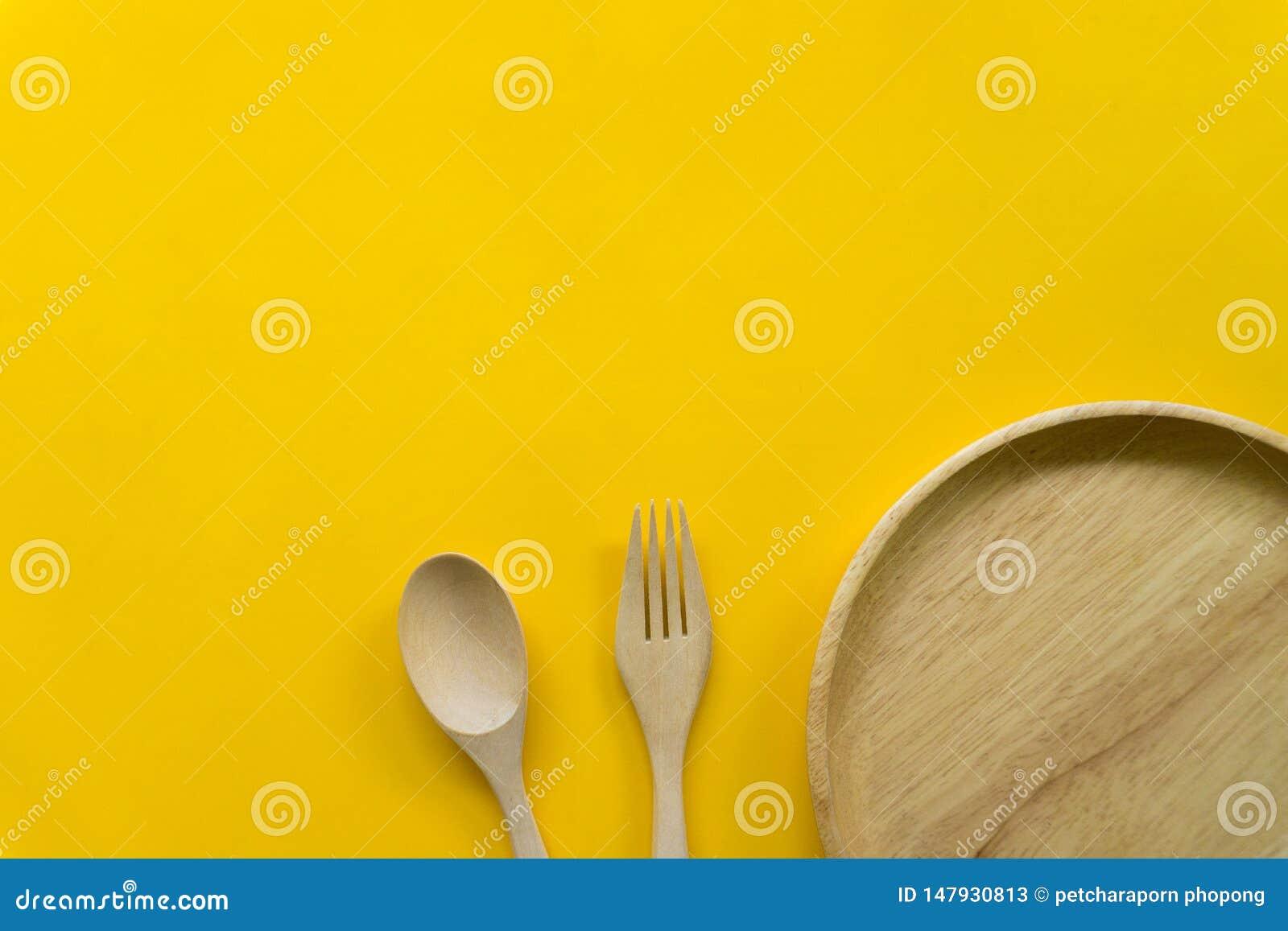 Sistema del artículos de cocina de la cuchara de madera y de la bifurcación de madera aisladas con el fondo amarillo