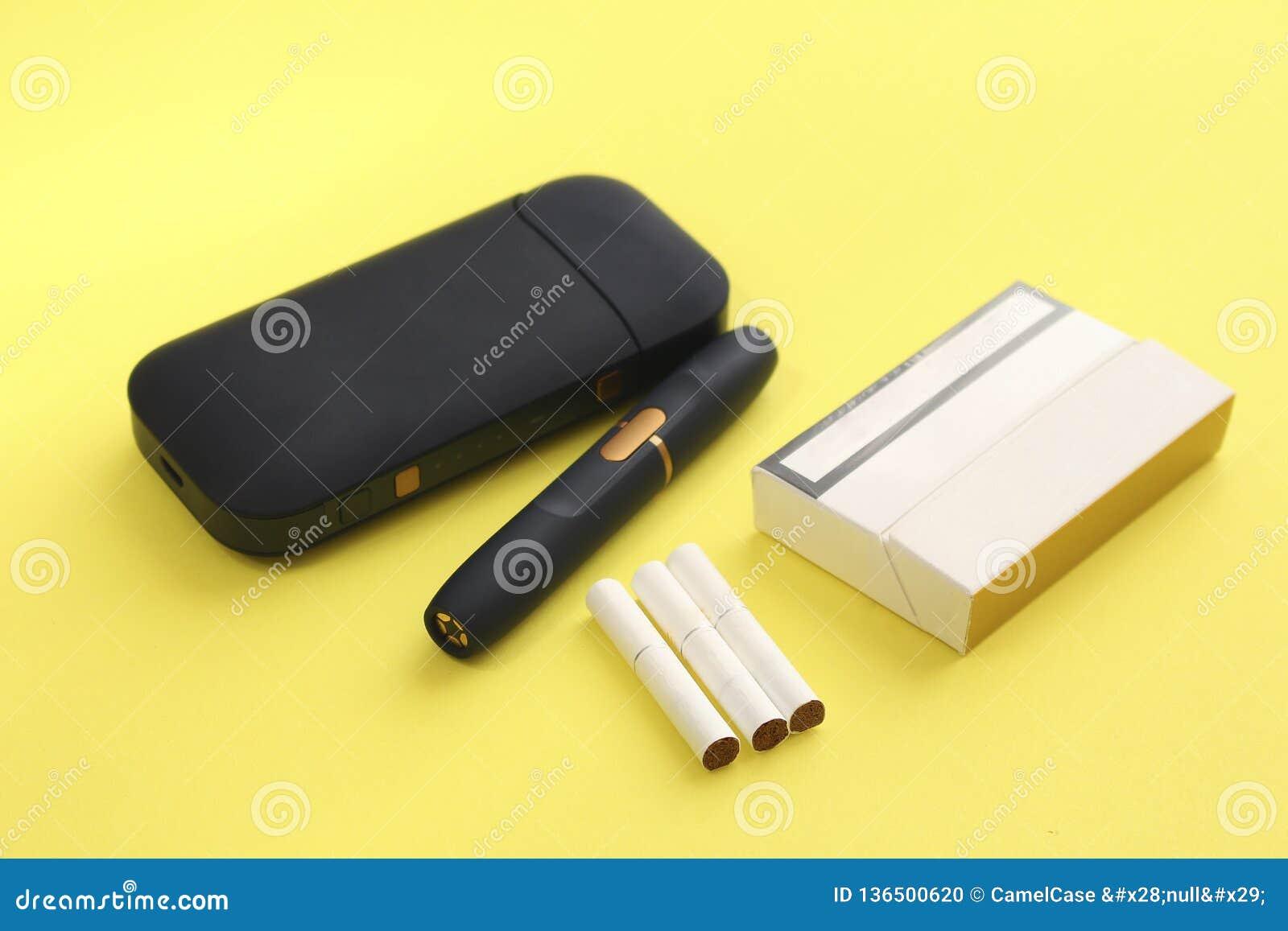 Sistema di riscaldamento di Tabacco, pacchetto della sigaretta e bastoni su fondo giallo