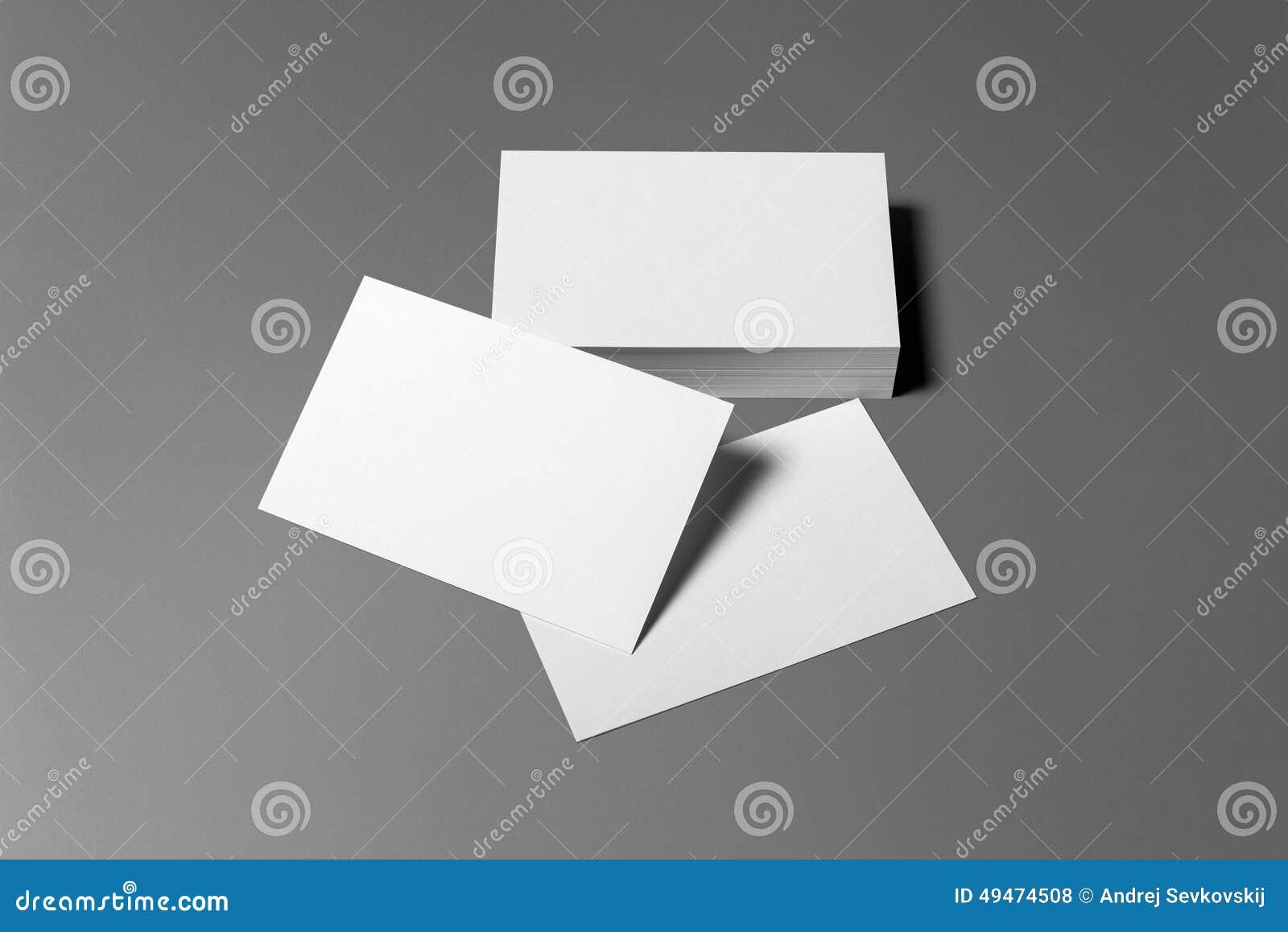 Sistema en blanco de los efectos de escritorio de las tarjetas de visita aislado en gris
