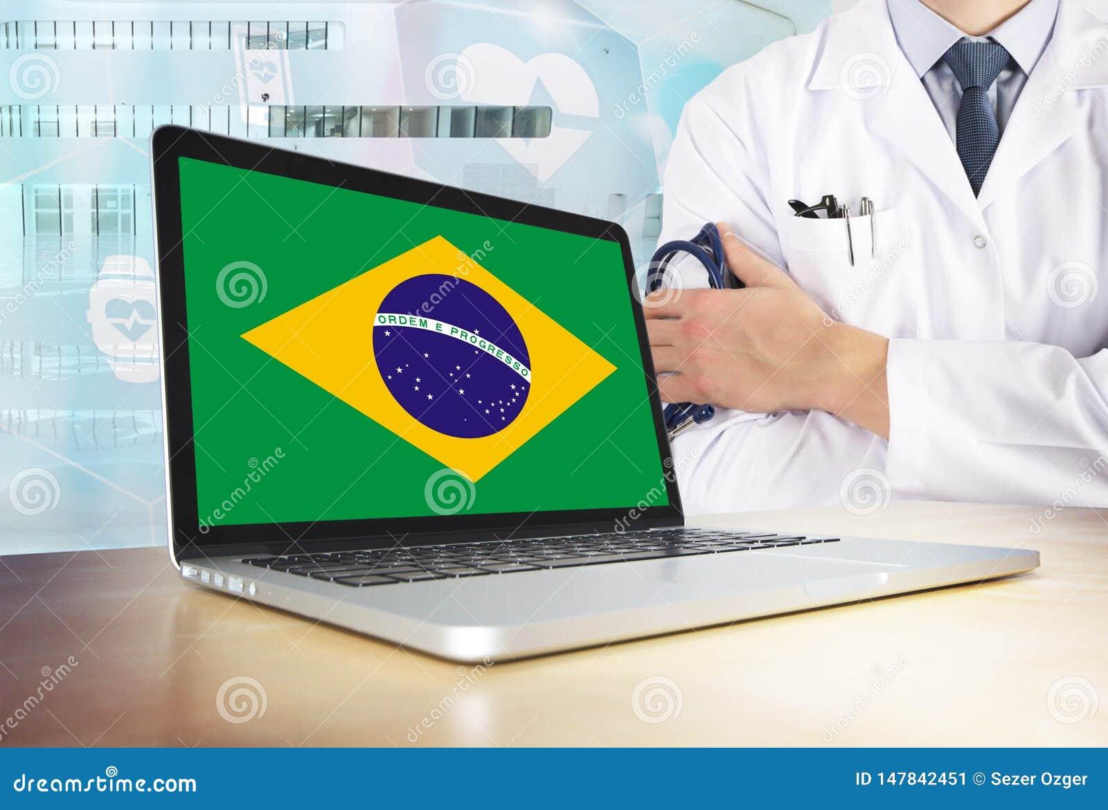 Sistema sanitario del Brasile nel tema di tecnologia Bandiera brasiliana sullo schermo di computer Medico che sta con lo stetosco