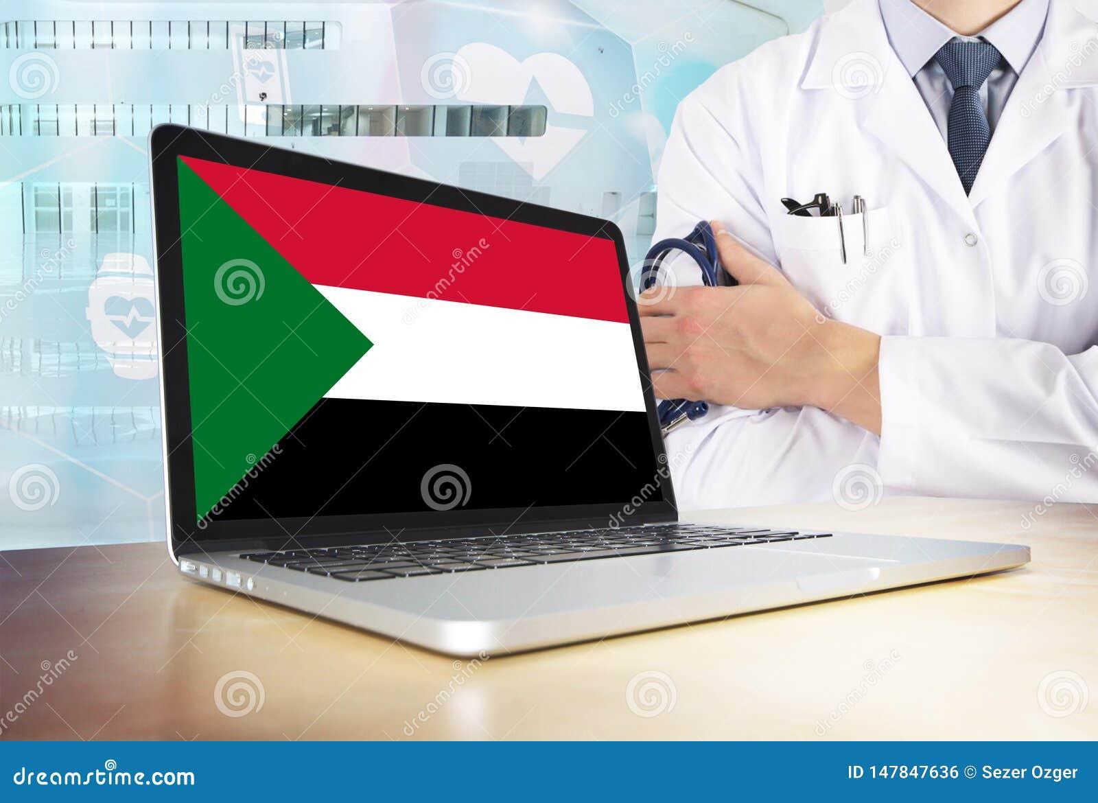 Sistema sanitario del Sudan nel tema di tecnologia Bandiera sudanese sullo schermo di computer Medico che sta con lo stetoscopio
