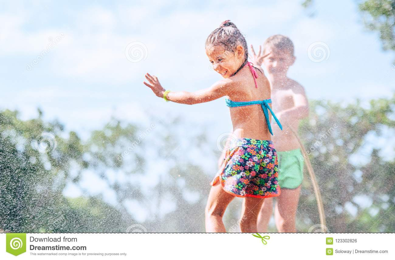 Sister and Brother play together with watering hose in garden