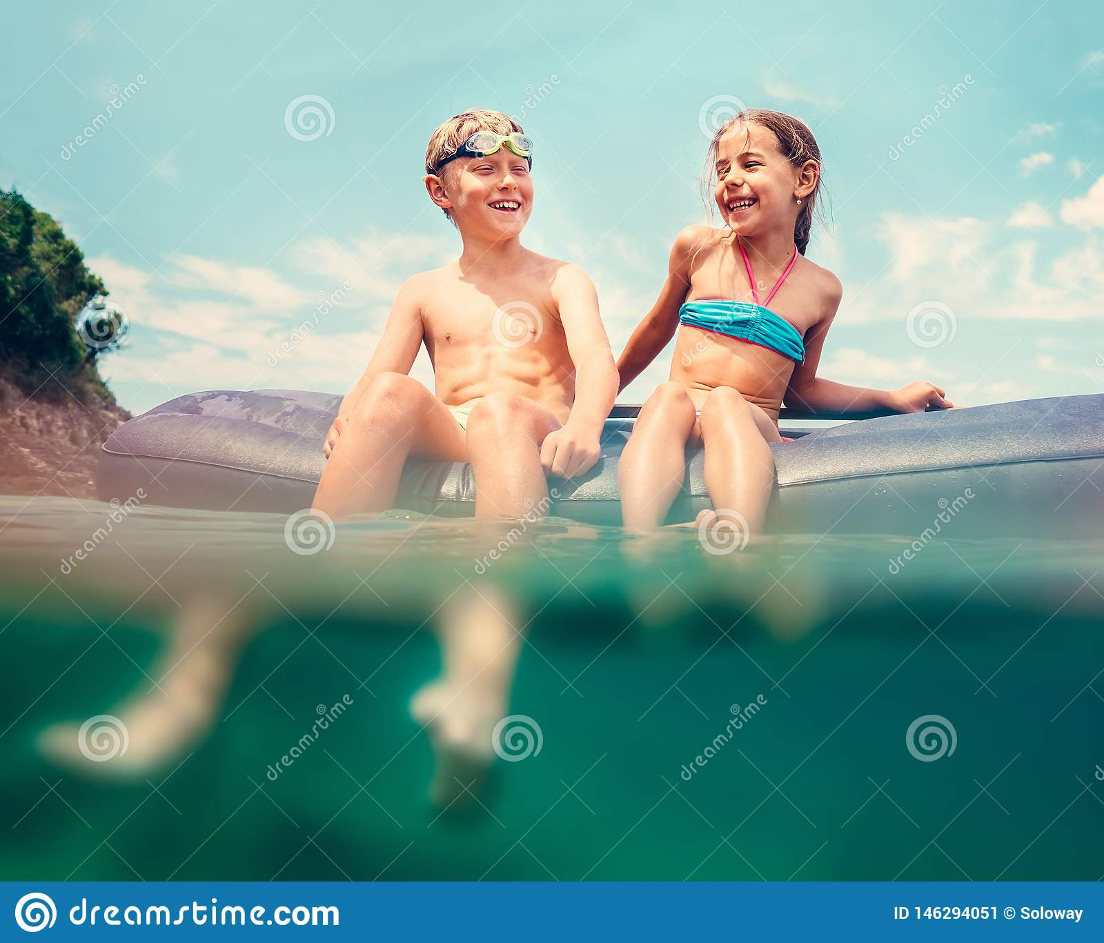 Sister and brother sitting on inflatable mattress and enjoying the sea water, cheerfully laughing when swim in the sea. Careless