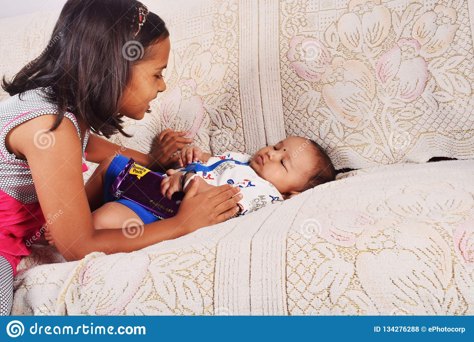 Sister playing with baby brother sleeping on sofa, Pune, Maharashtra.