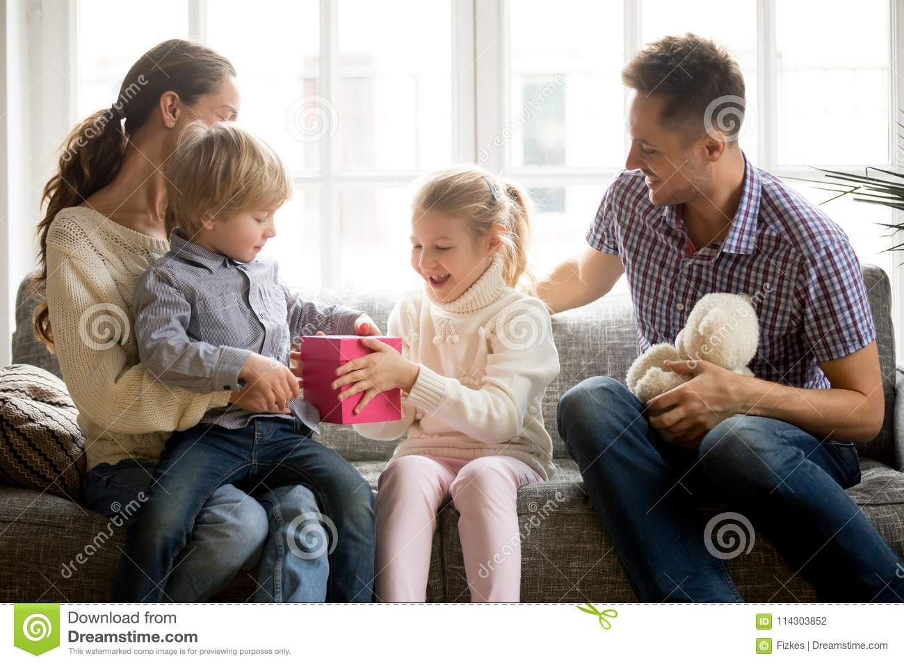 Sister Presenting Gift For Little Brother Giving Cute Boy Box With Present Excited Kid Girl Making Surprise Congratulating Happy Family And