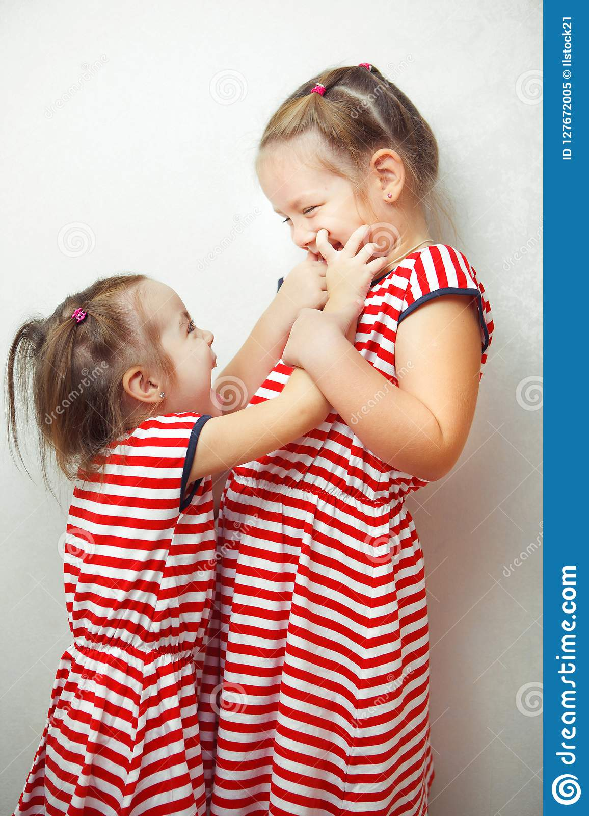 Sisters With Hairstyles And Same Dresses Having Fun Stock Image