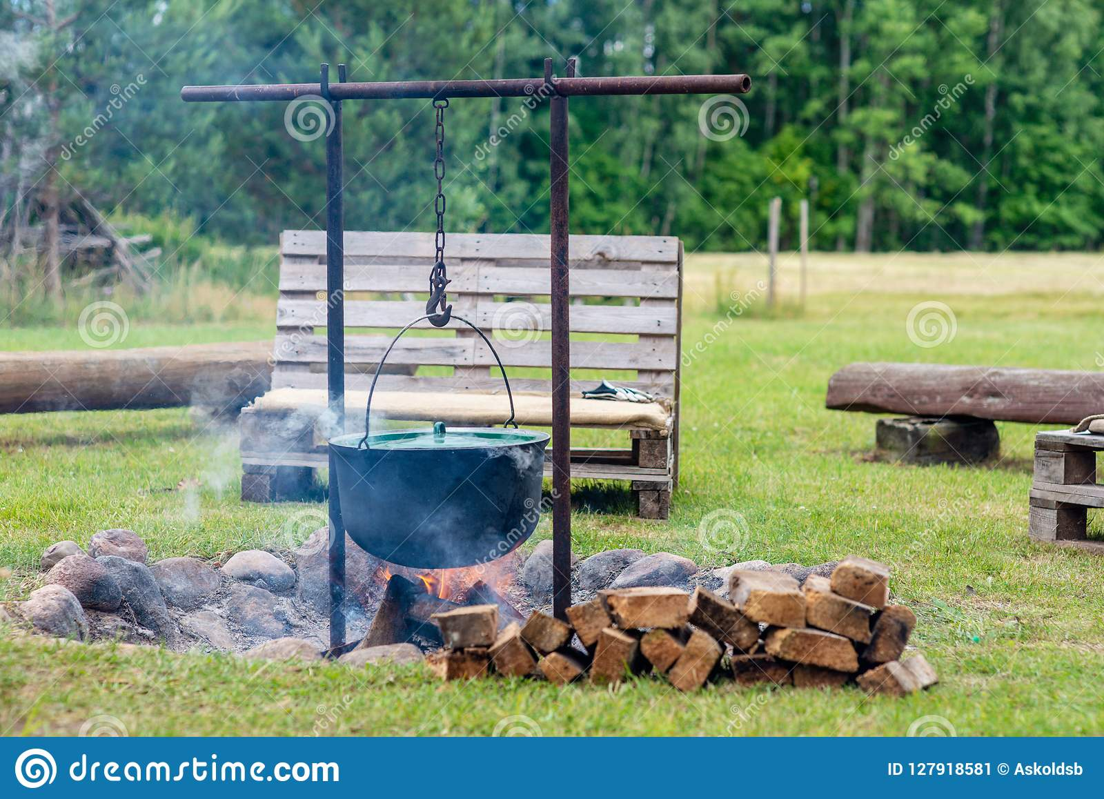 Site de feu de camp avec les bancs en bois près de la maison de campagne