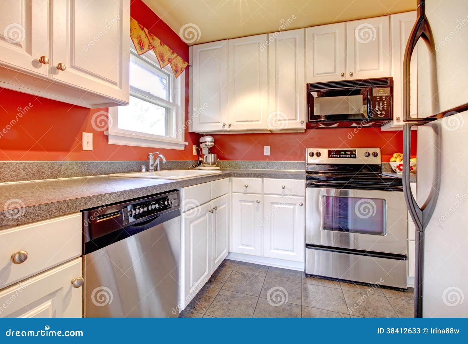 Sitio acogedor de la cocina con la pared roja y los for Cocinas con gabinetes blancos