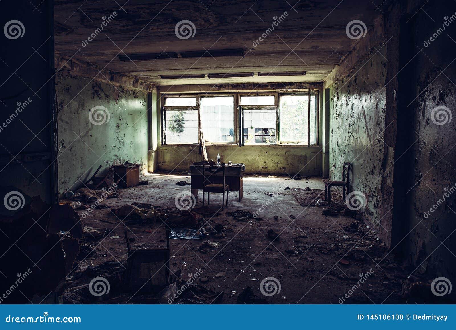 Sitio arruinado abandonado de construcción industrial dentro del grunge sucio interior, oscuro y de la atmósfera espeluznante