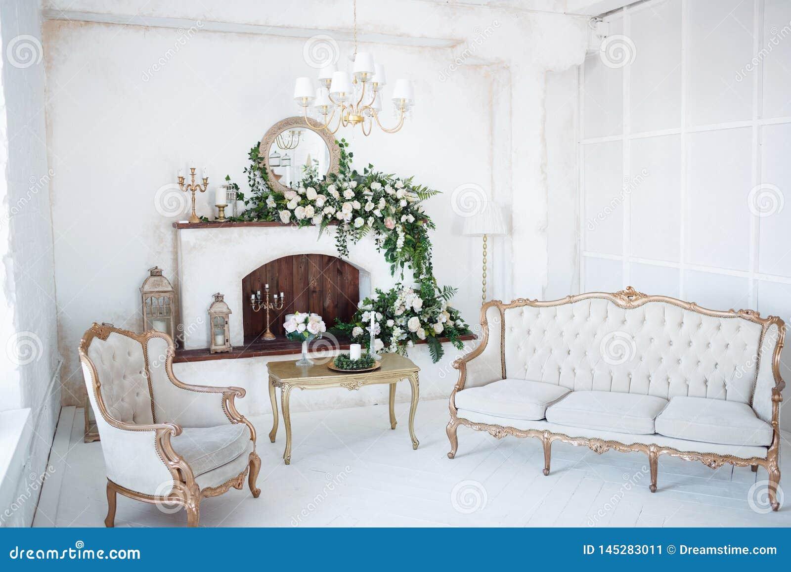 Sitio blanco con la chimenea y muebles tallados
