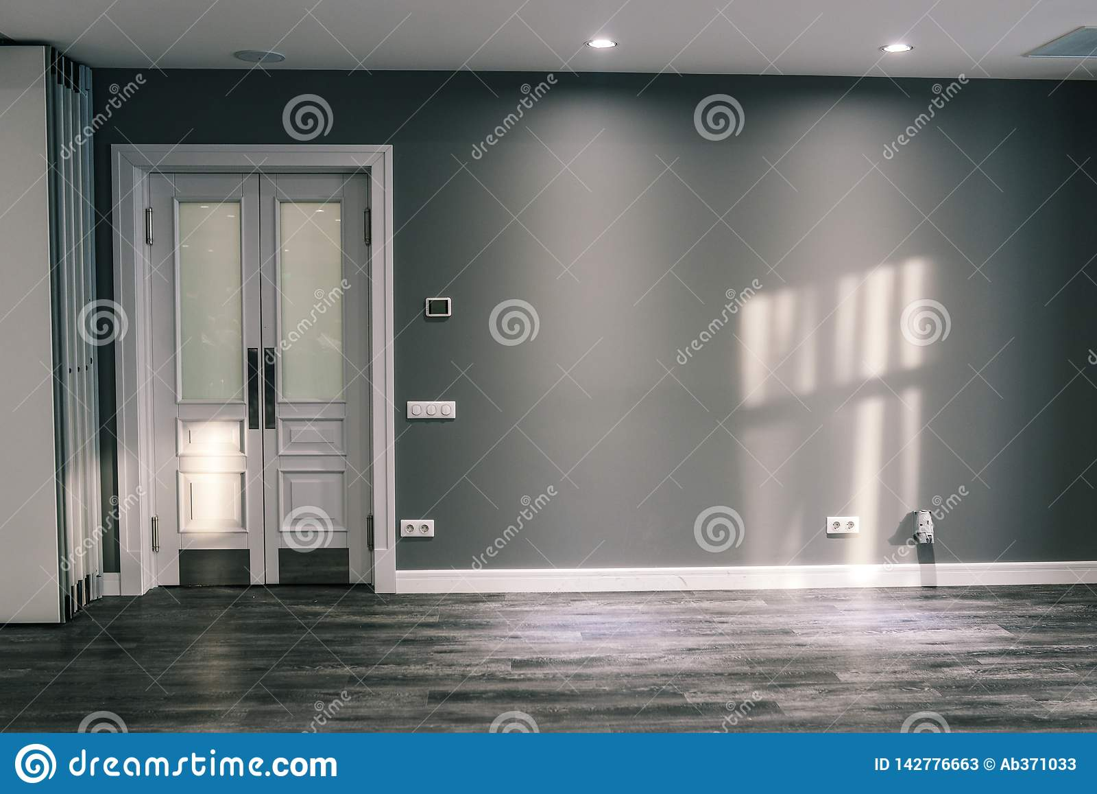 Sitio con una pared gris y una puerta blanca Puerta de cristal con el ribete En el resplandor del sol del piso y de la pared Colo