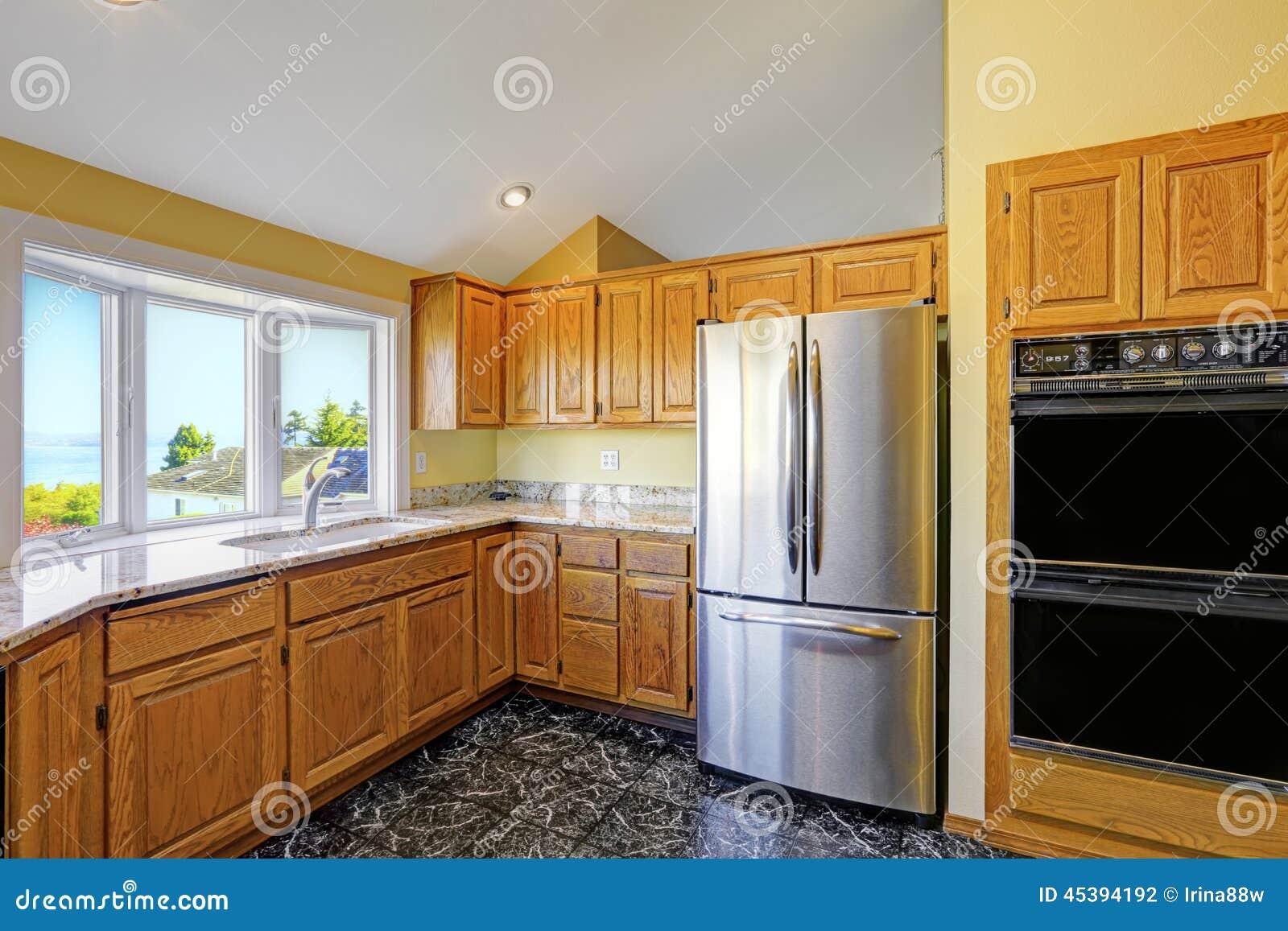 Sitio de la cocina con los tops del granito y el suelo de baldosas negro