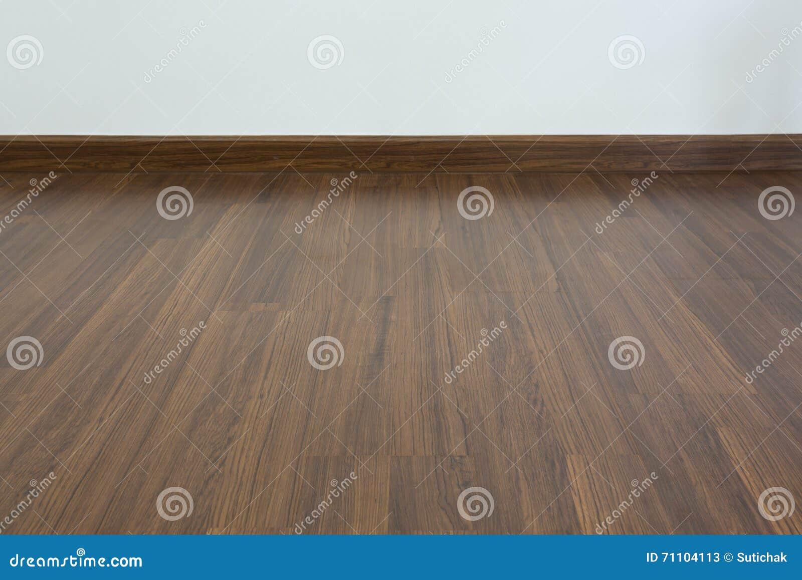 Sitio vacío, fondo blanco de la pared del mortero y piso laminado de madera