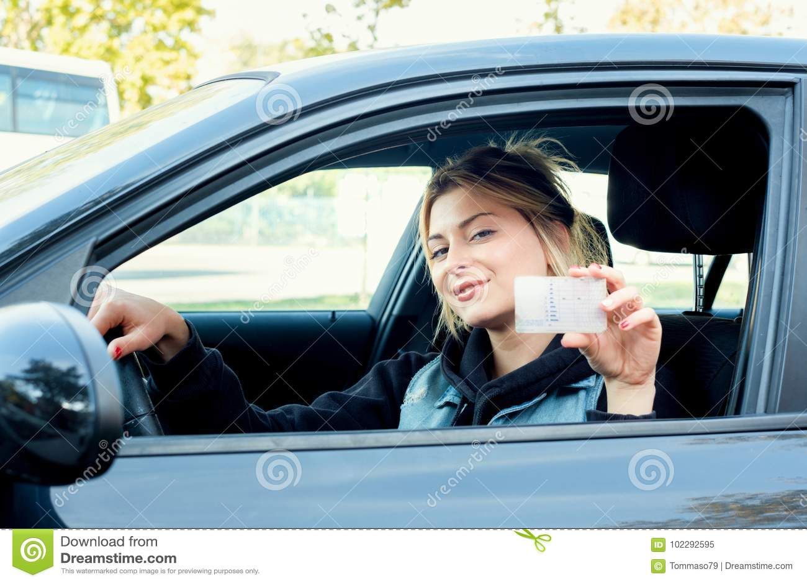 Sititng del ritratto della ragazza nella sue automobile e patente di guida