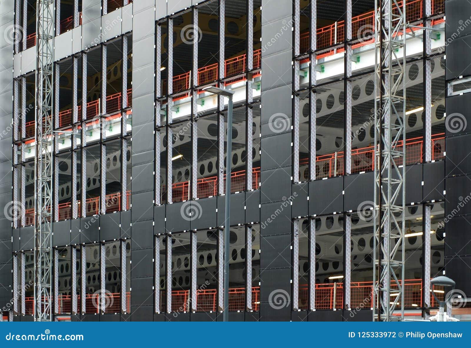 Sito dell edificio urbano con rivestimento che è fissato alla struttura del metallo di grande sviluppo commerciale con il recinto