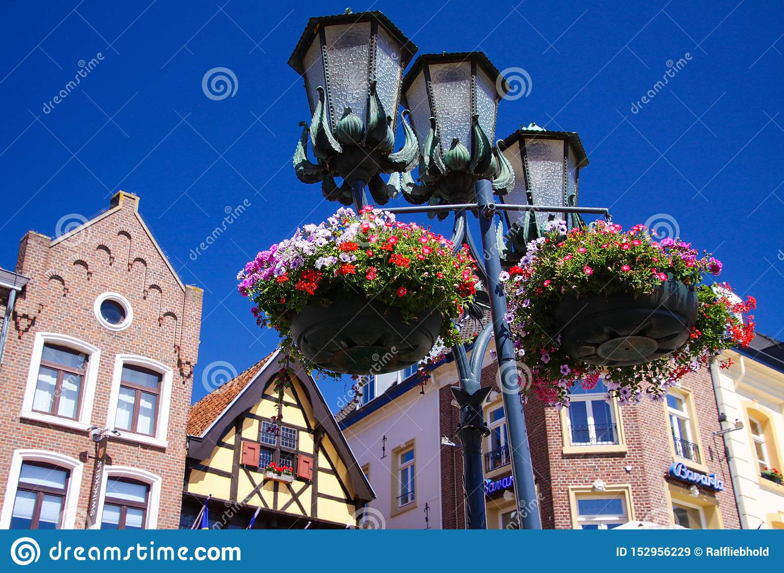 SITTARD, NETHERLANDS - JUIN 29. 2019: Low angle view on street lamps decorated with flower baskets against blue sky with medieval