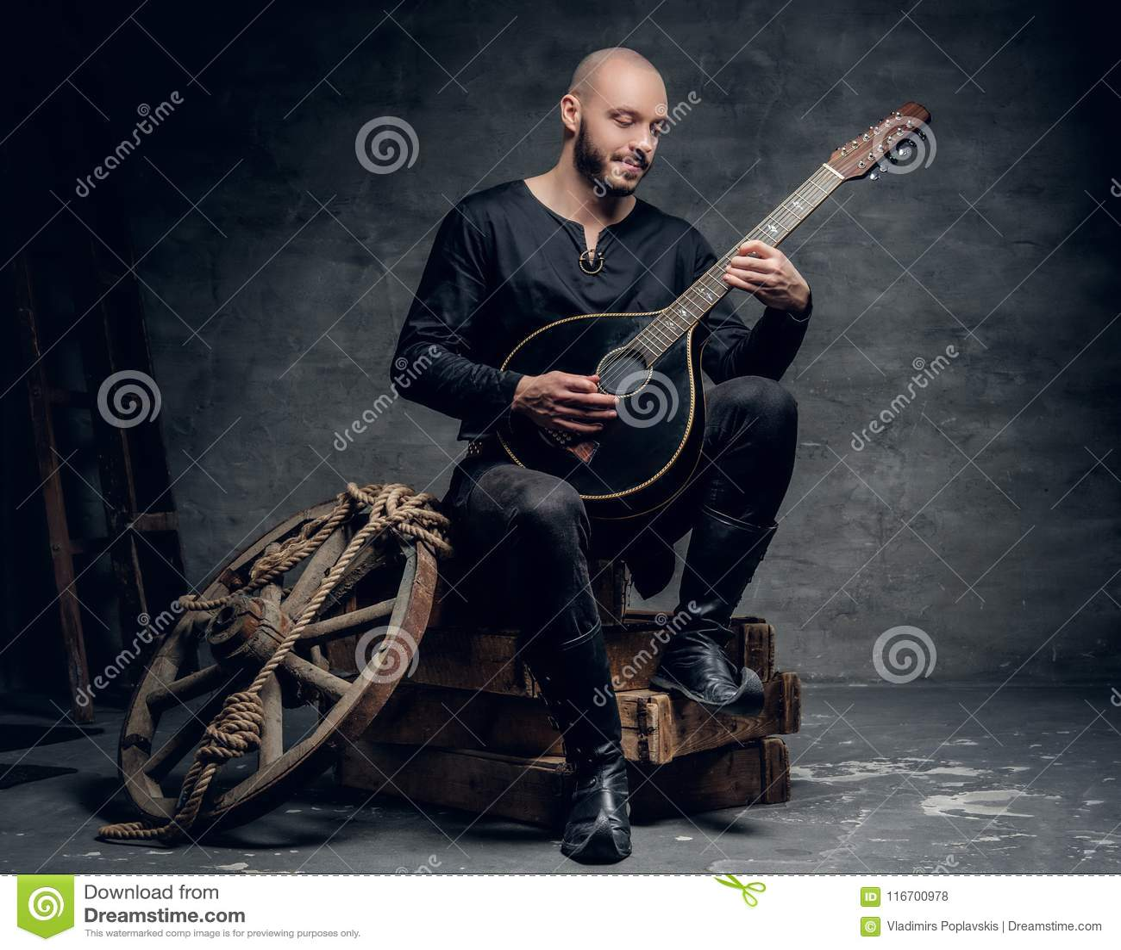 Sitter spelar keltisk kläder för traditionell tappning för spelman iklädd på en träask och mandolinen