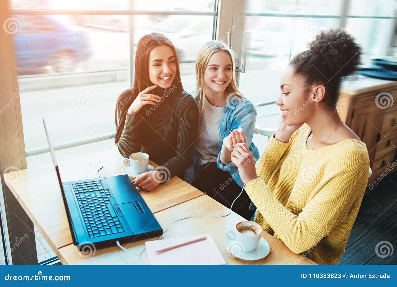 Sitter talar unga kvinnor för träd tillsammans i ett litet kafé med stora fönster och med de Ett av dem är