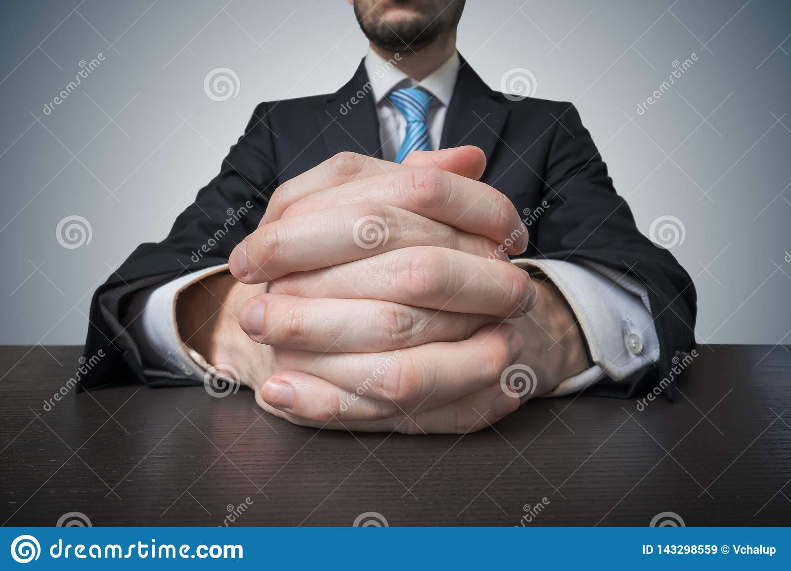 Sitting businessman with clasped hands. Negotiation and dealing concept.