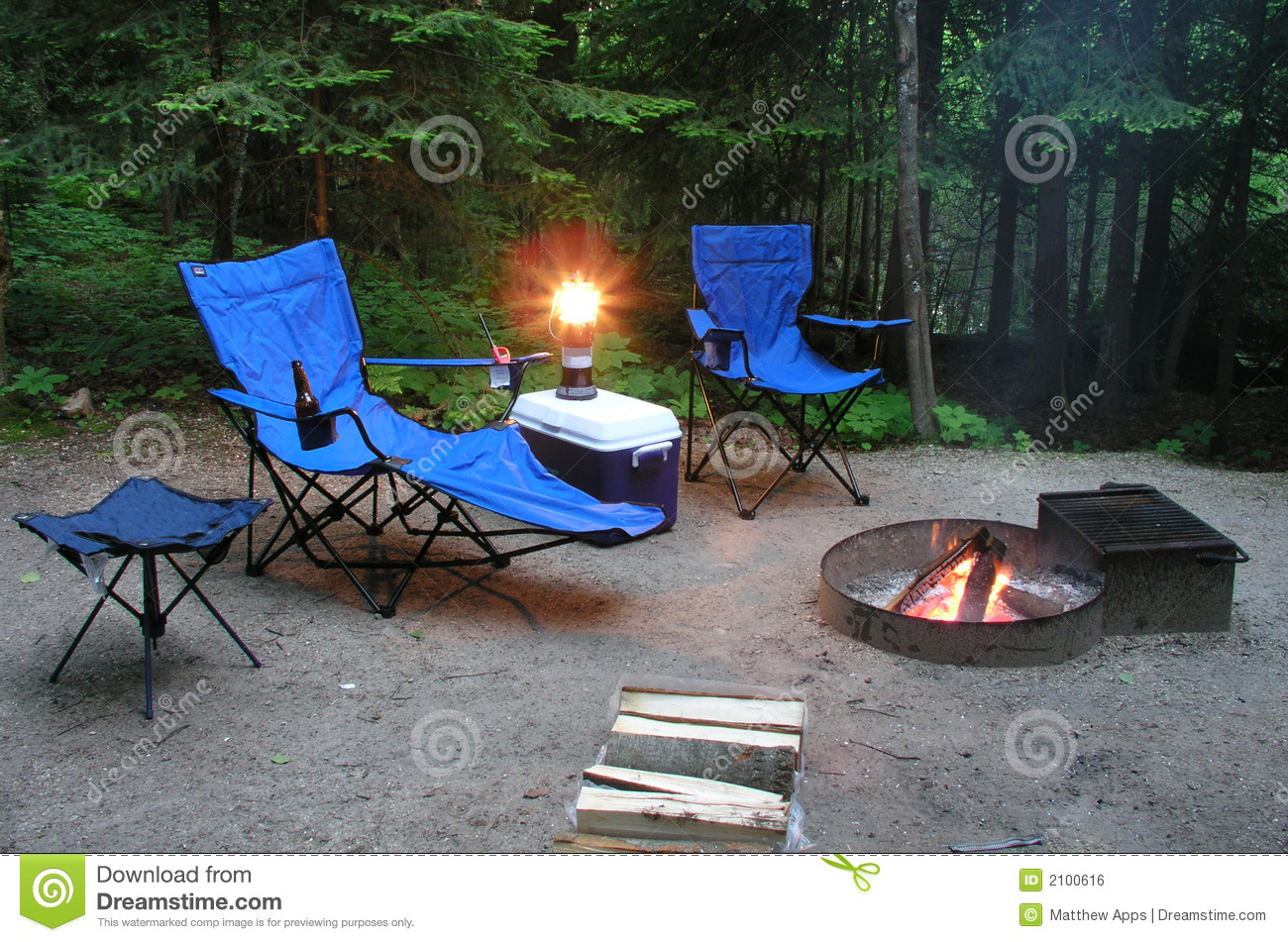 Superieur A Camping Scene With 2 Lawn Chairs, A Cooler, Table, Lantern And A Campfire  With Wood At A Campsite.