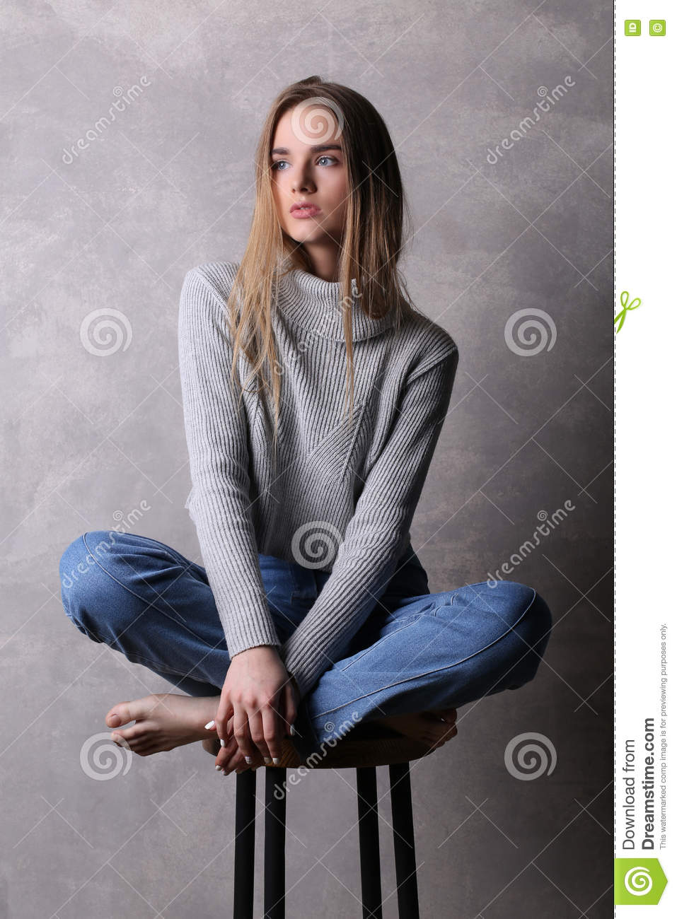 Sitting Girl In Sweater With Crossed Legs Gray Background