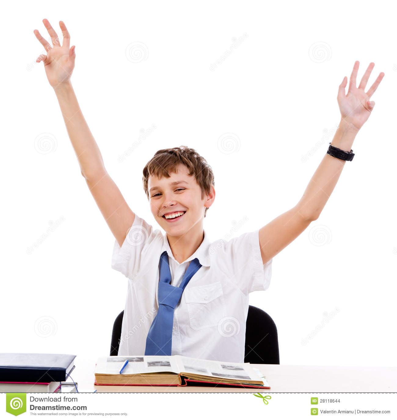 Student male with hands raised and big smile, sitting behind the desk.