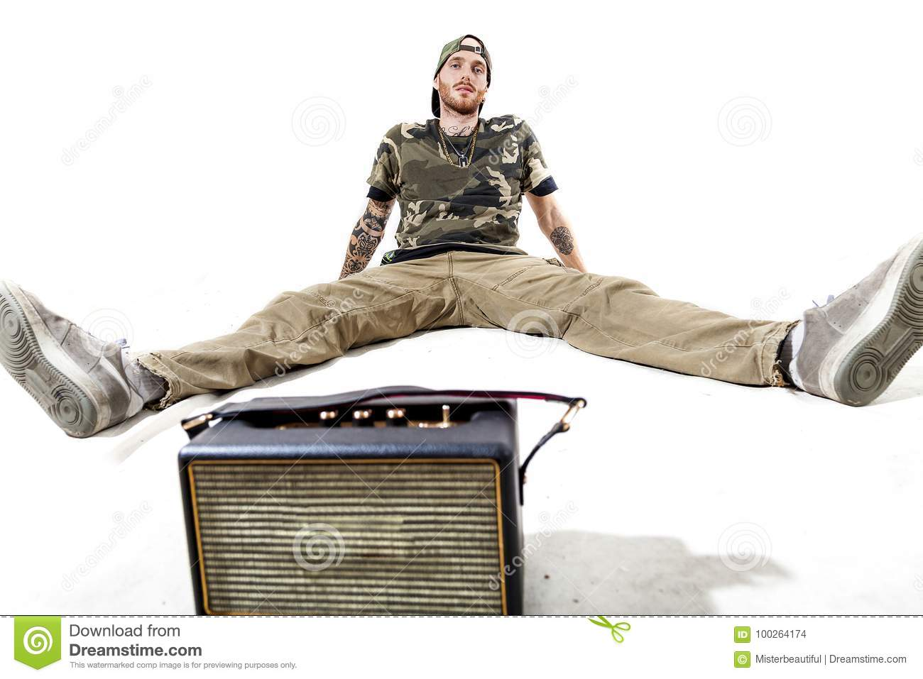 Rapper With Z Tattoed On His Face: Sitting Tattooed Rap Singer Posing In Studio Stock Photo