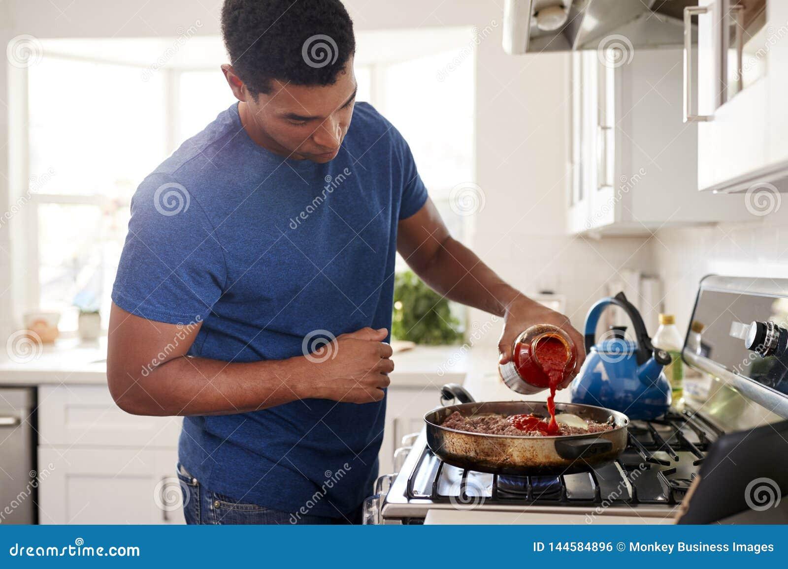 Situación afroamericana adulta joven del hombre en la cocina que cocina en el avellanador, añadiendo una salsa al sartén, cierre