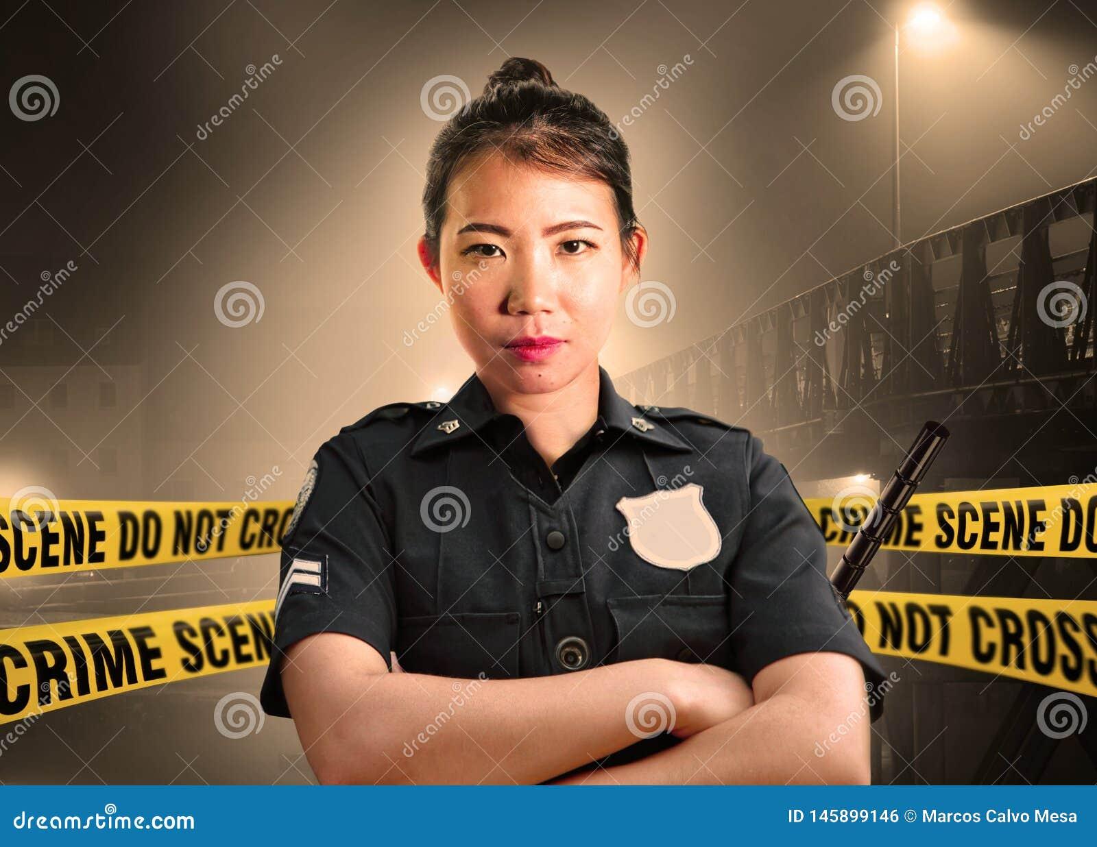 Situación americana asiática joven del oficial de policía seria en la custodia de la escena del crimen para preservar pruebas en