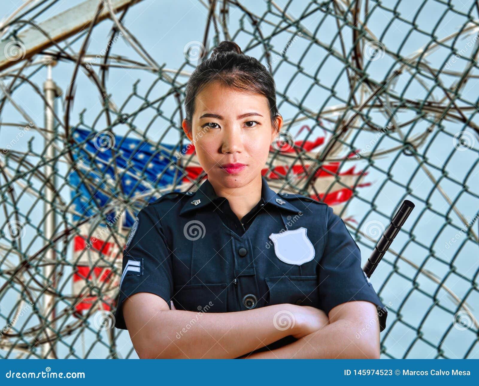 Situación americana asiática seria y atractiva joven de la mujer del guardia en la policía que lleva de la cerca del barbwire de