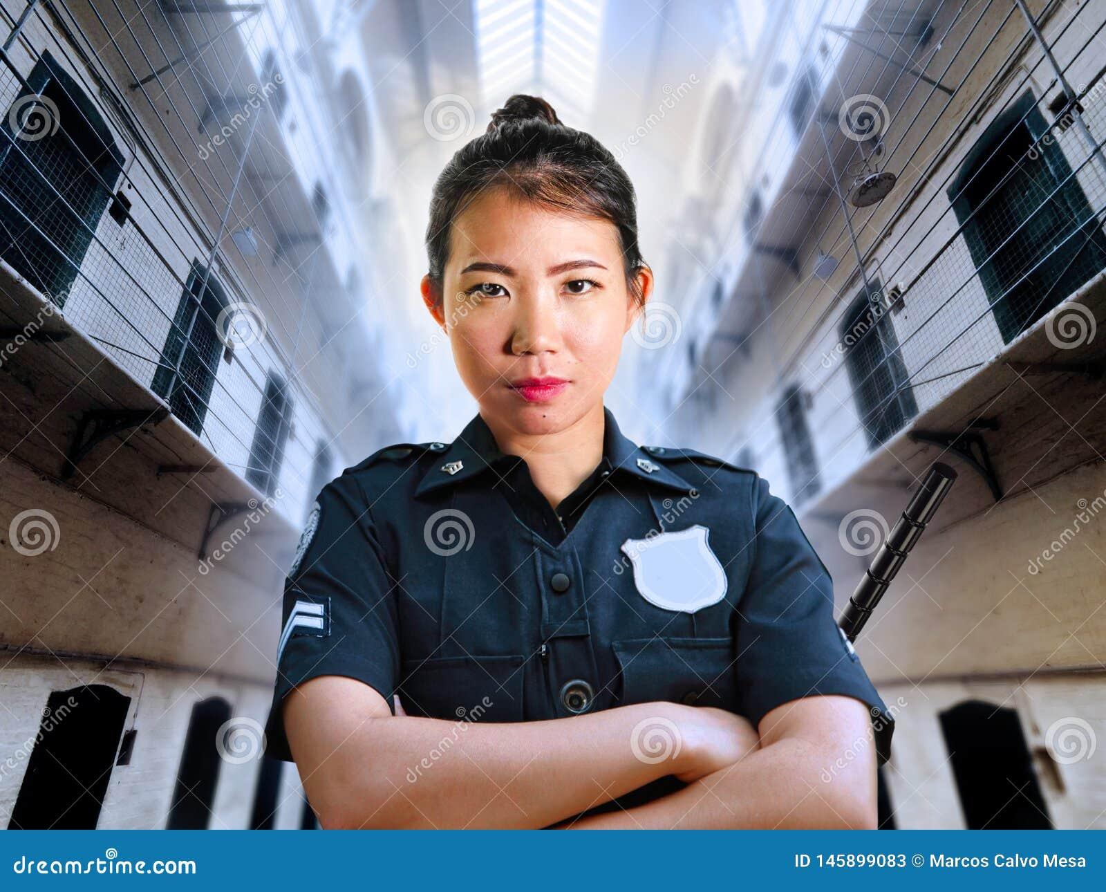 Situación china asiática seria y atractiva joven de la mujer del guardia en el uniforme de la policía del pasillo de la prisión d