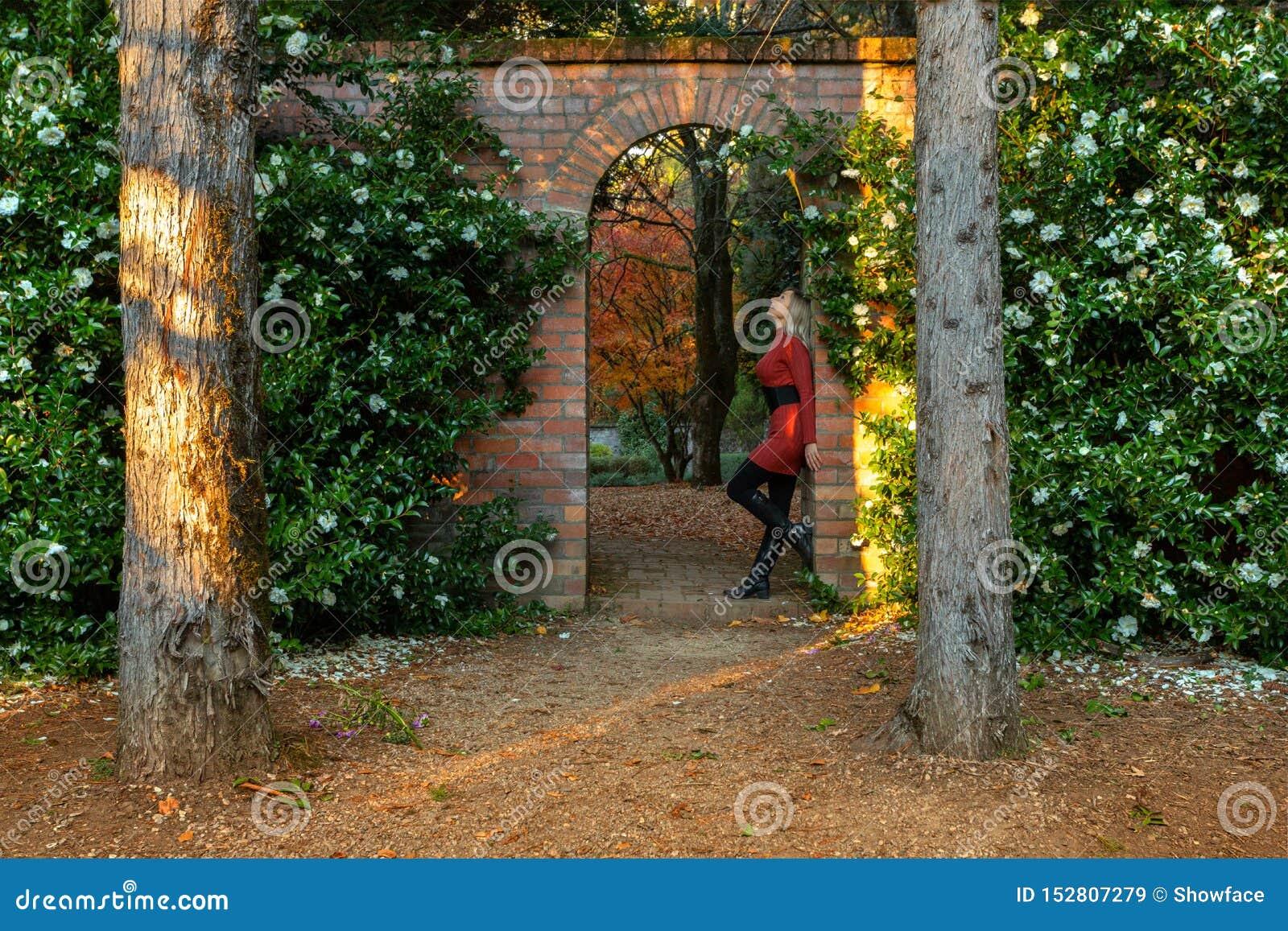 Situación de la mujer en arco de piedra hermoso del jardín
