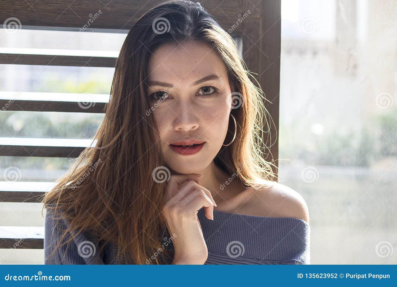 Situación hermosa de la mujer en una ventana de madera