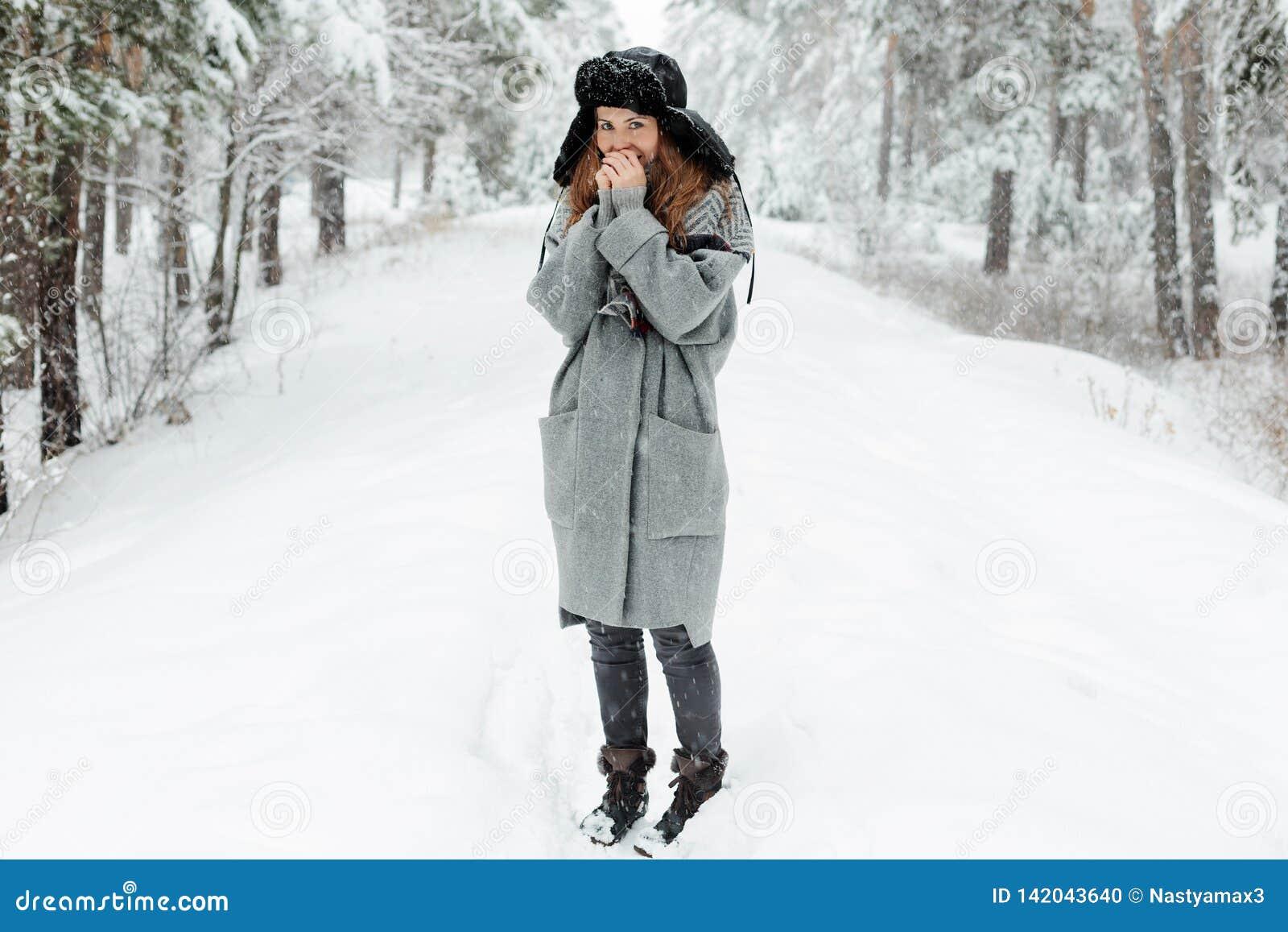 Situación hermosa de la mujer joven entre árboles nevosos en bosque del invierno y nieve del goce