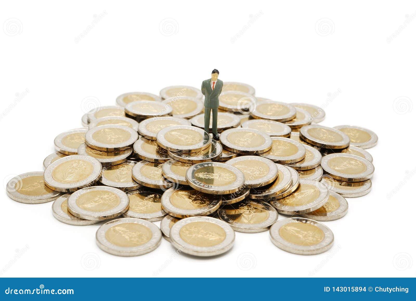 Situación miniatura de la gente en la pila de nuevas 10 monedas del baht tailandés