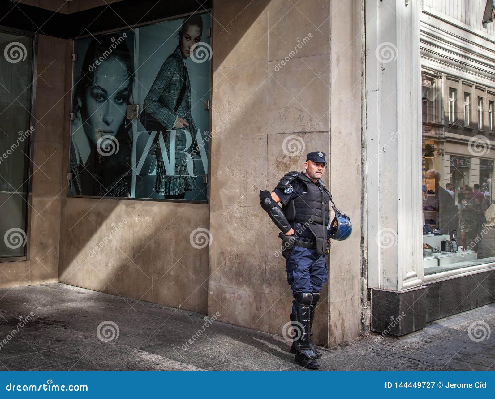 Situación servia del policía delante de una tienda de la moda con los antidisturbios antis en el centro de Belgrado, Serbia, dura