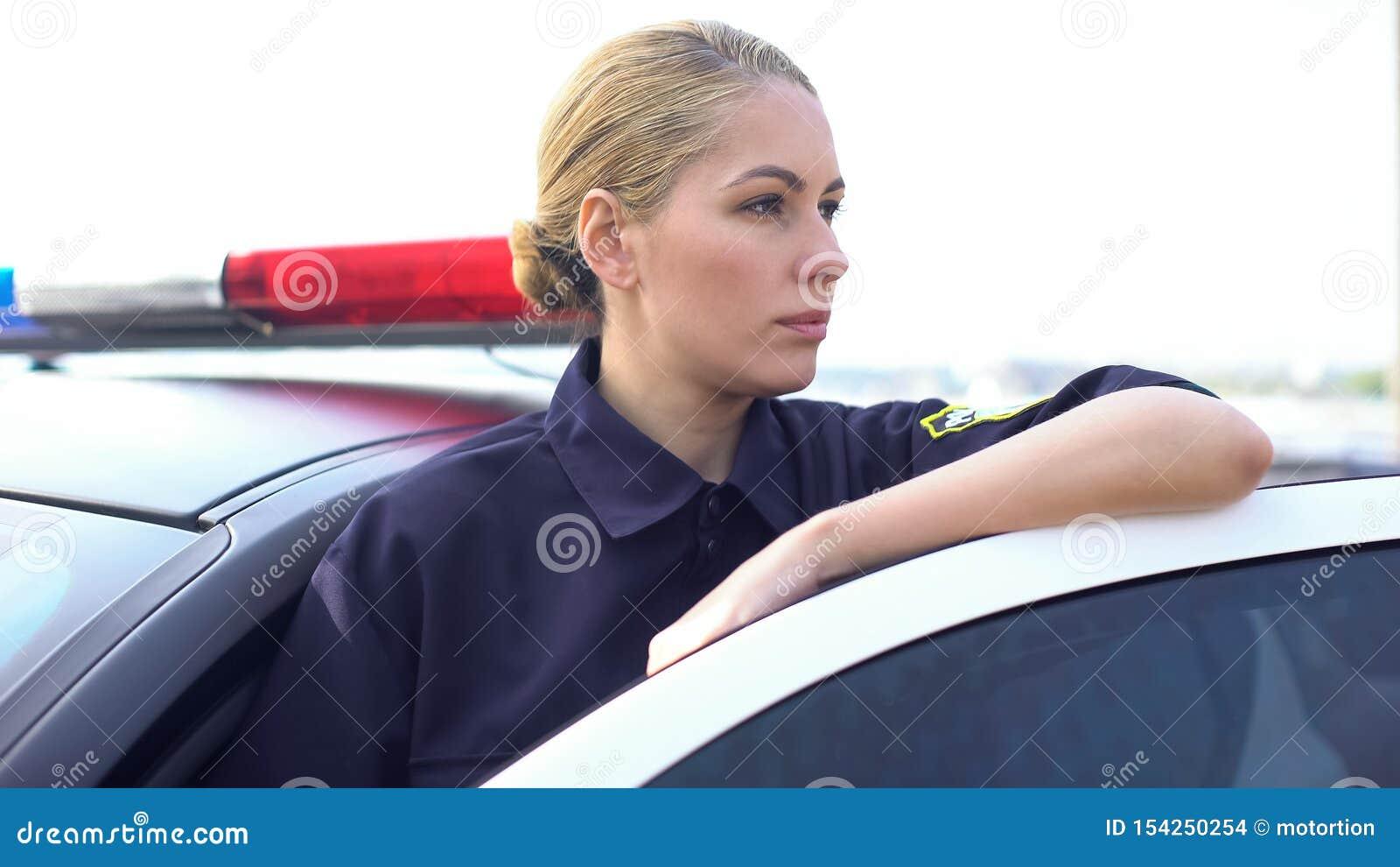 Situación valiente cerca del coche patrulla, protección de la mujer policía del orden público en ciudad