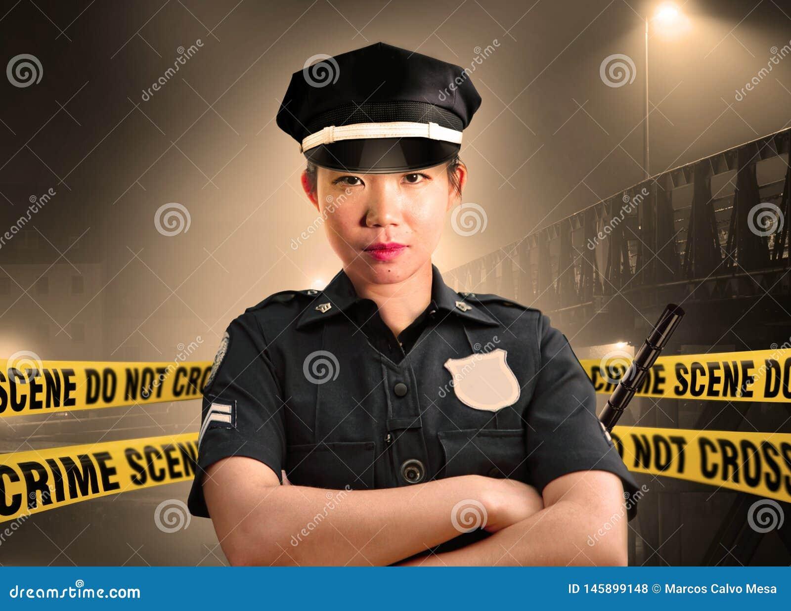 Situaci?n americana asi?tica joven del oficial de polic?a seria en la custodia de la escena del crimen para preservar pruebas en