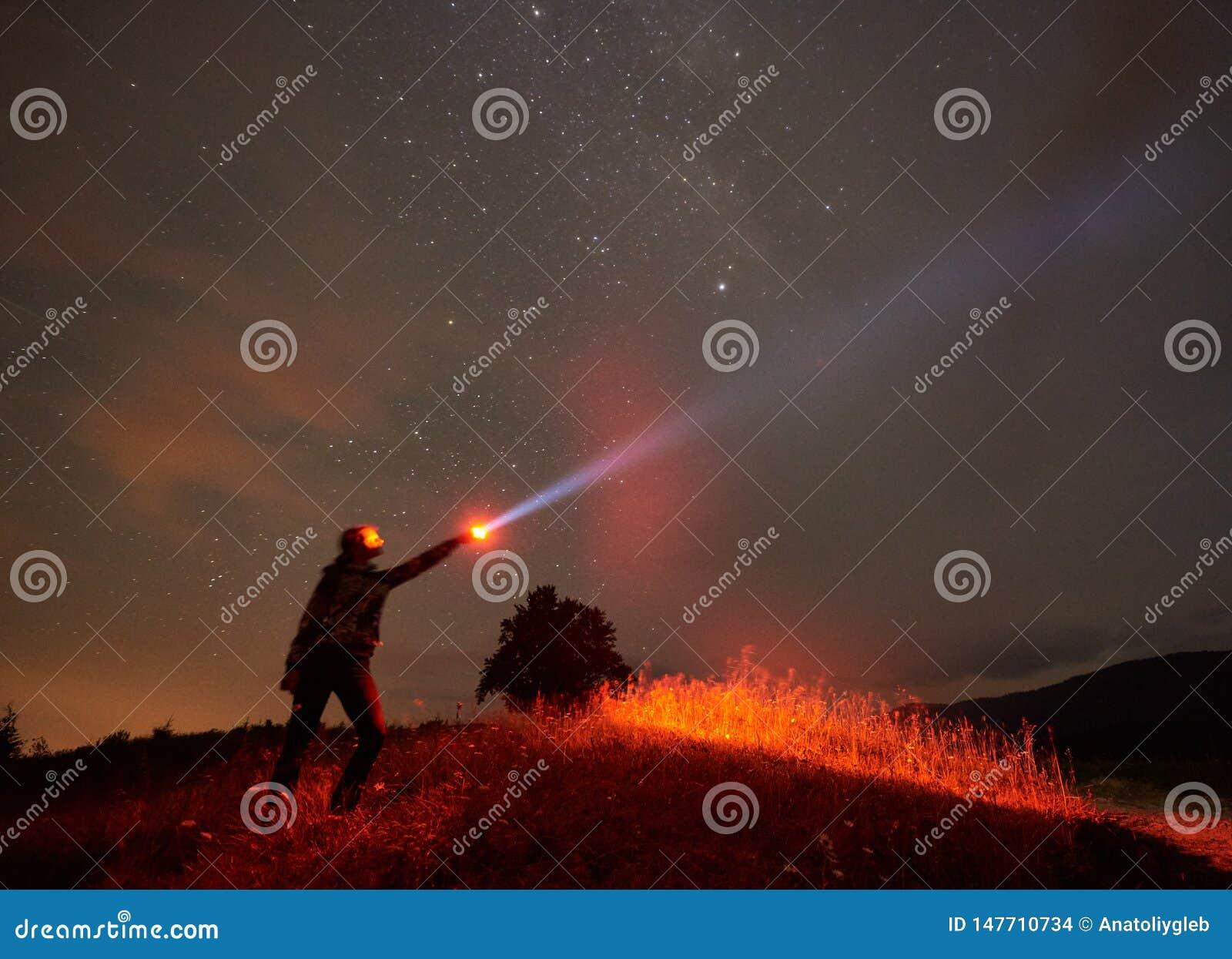 Situaci?n de la mujer contra el cielo estrellado de la noche en las monta?as con una linterna en su mano