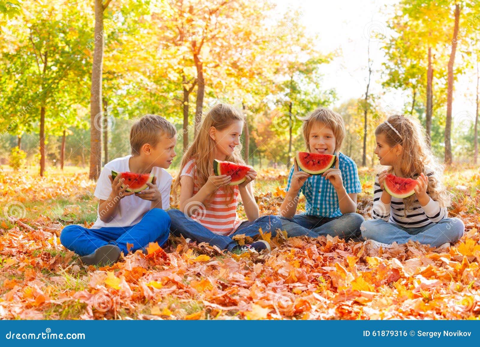 sitzende kinder die wassermelone und das essen halten stockfoto bild von vier freunde 61879316. Black Bedroom Furniture Sets. Home Design Ideas