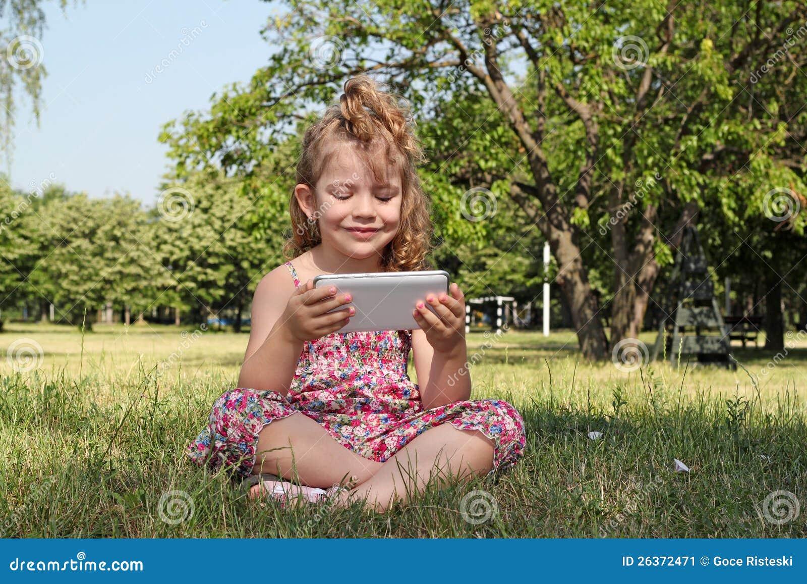 Sitzendes Spiel des kleinen Mädchens mit Tablette
