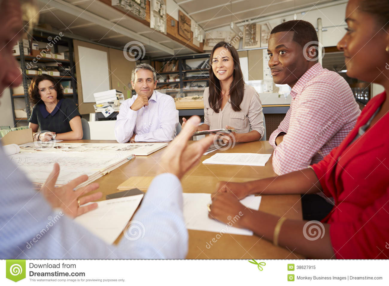 Six architects sitting around table having meeting royalty for Sitting table designs