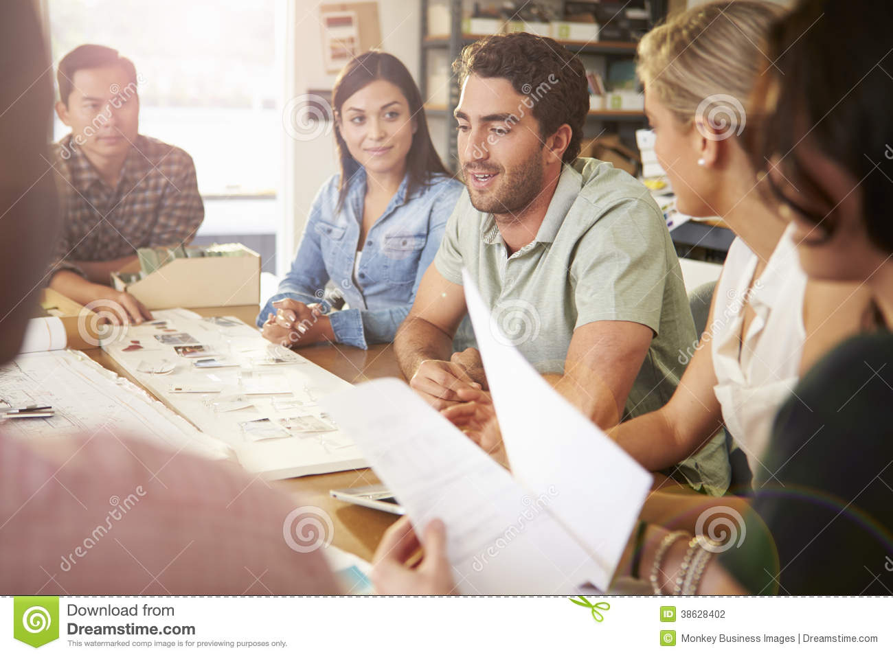 Six architects sitting around table having meeting stock for Sitting table designs