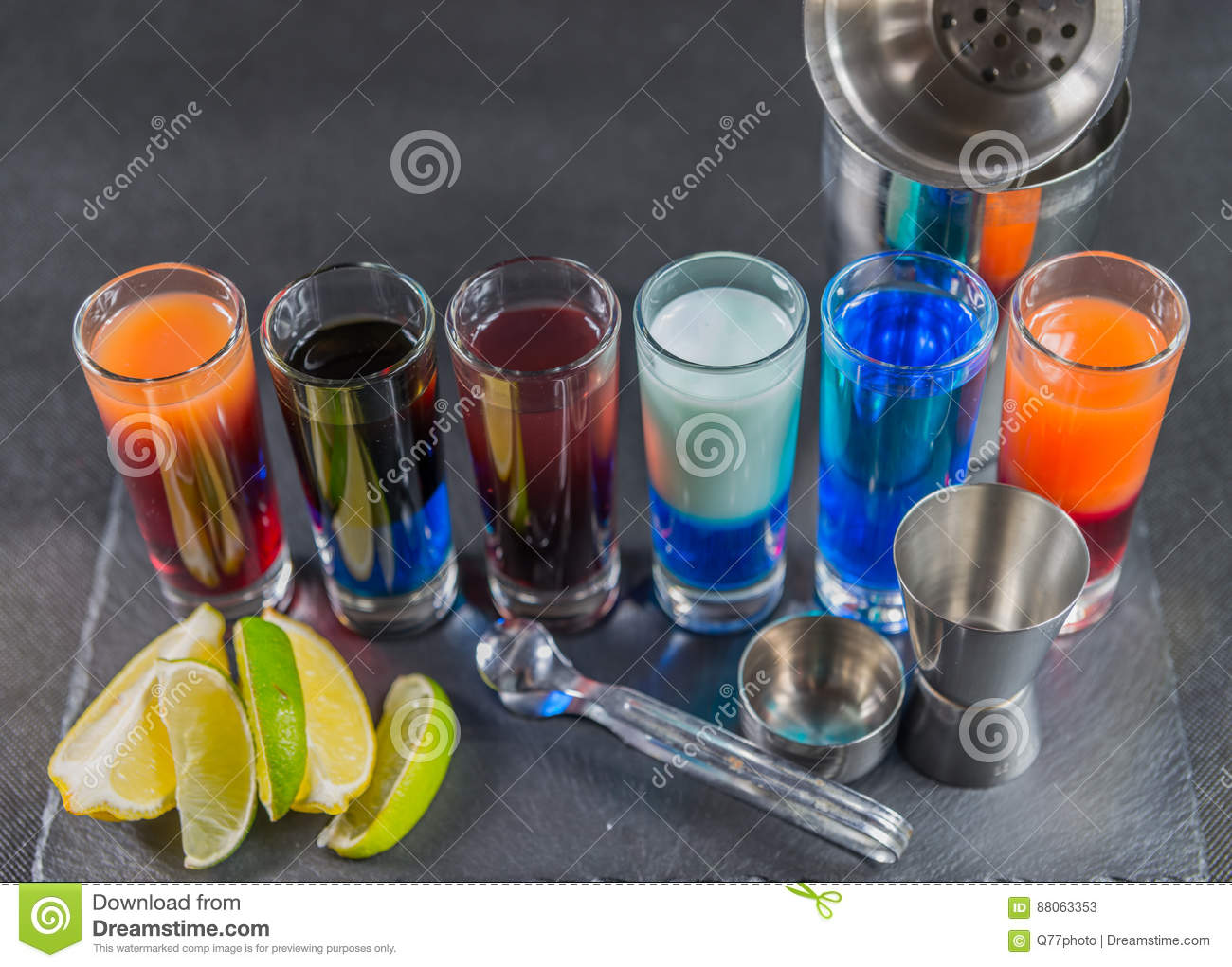 six different colored shot drinks, lined up on a black stone plate, ice cubes in shaker and ice tongs, lemon and lime