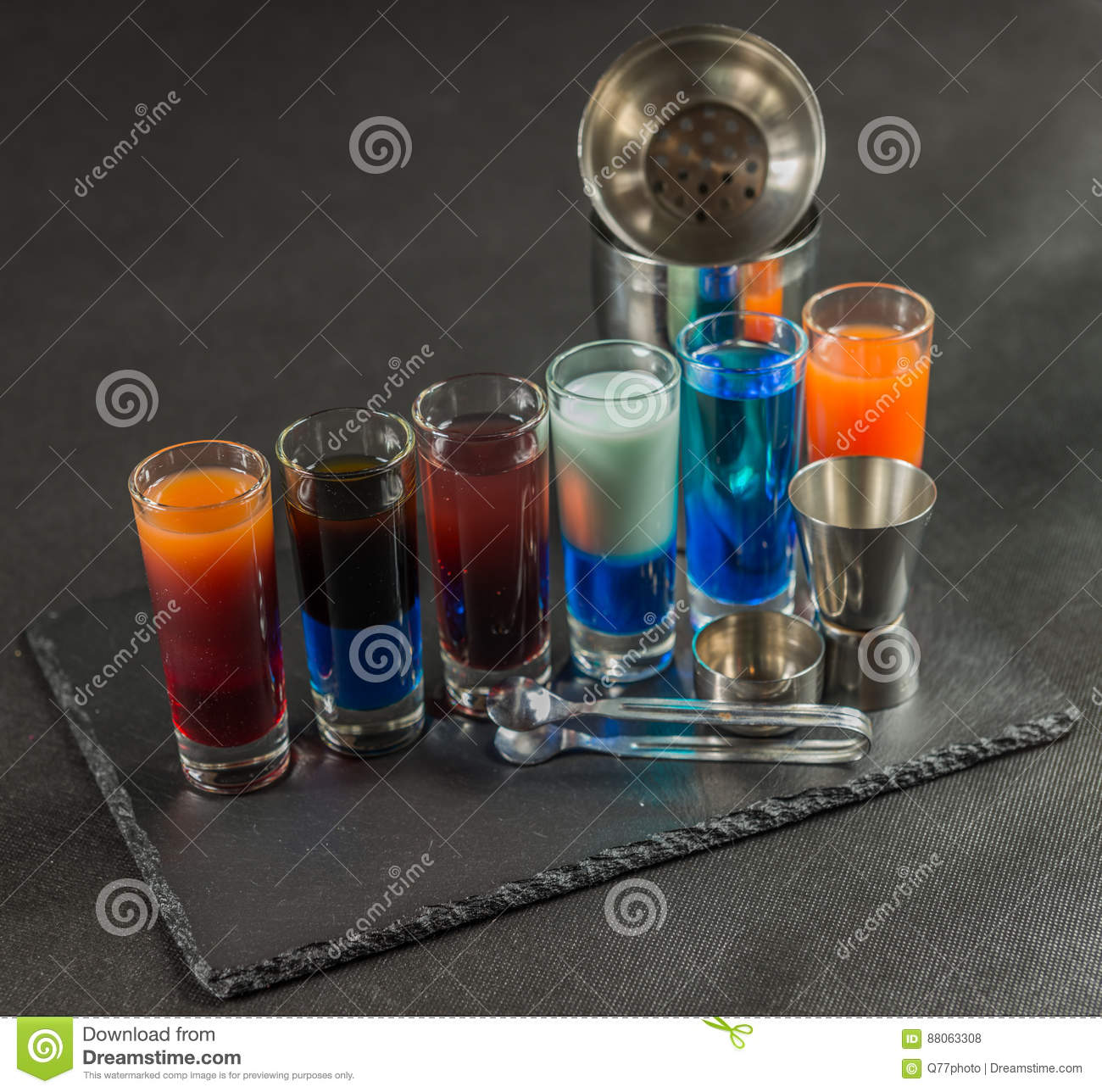 six different colored shot drinks, lined up on a black stone plate, ice cubes in shaker and ice tongs