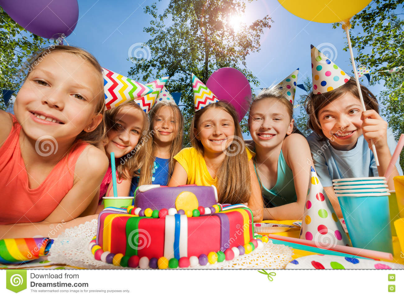 Six happy kids in party hats around birthday cake